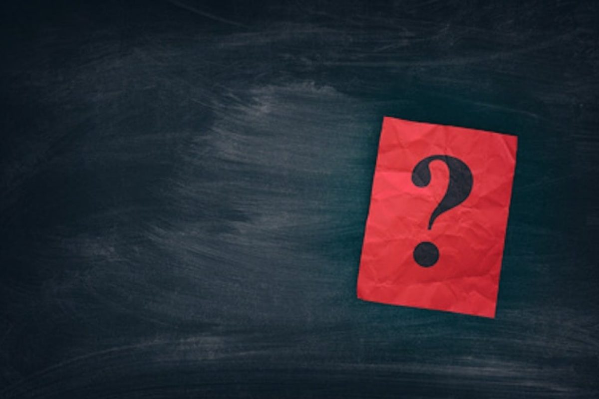 Red paper note with question marks on black board. Close up.
